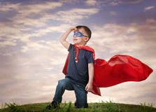 A boy in a Superman costume. Stands on the grass in a red cloak stock photos