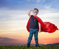 A boy in a Superman costume stands. On the grass in a red cloak royalty free stock photo