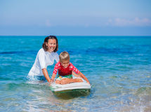 Boy with surf. Little boy with his mother learning surfing Royalty Free Stock Image