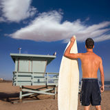 Boy surfer back view holding surfboard on beach. Boy surfer back rear view holding surfboard on santa Monica Lifeguard house California Stock Images