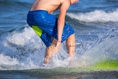 Boy surfer surfing waves on the beach. Enjoying fun Stock Image