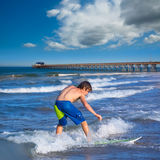 Boy surfer surfing waves on the Newport beach. Boy surfer surfing waves on Newport pier beach California Royalty Free Stock Photography