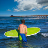 Boy surfer waiting for the waves on the beach Stock Photos