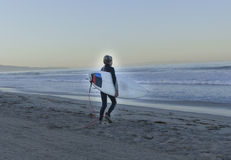 Boy Surfer Walking Into Ocean. Boy surfer 'GROM' walking into the ocean just as the sun is rising with dawn light Royalty Free Stock Photos