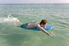 Boy surfing in the sea Stock Photography