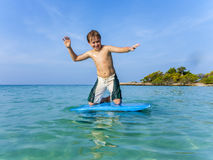 Boy surfing in the sea Stock Photos