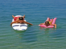 Boy surfing and sister on matrass. Boy lying (floating) on surfs desk take with hands with sister on pink air mattress spending holidays at Adriatic sea (Croatia Stock Image
