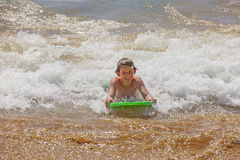 Boy surfing in the waves of the ocean. Happy boy surfing in the waves of the ocean stock images