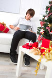 Boy surfs on laptop in Christmas Stock Photo