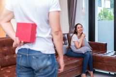 Boy surprise his Asian girlfriend by holding gift box behind him at their home. Valentine`s day and pre wedding honeymoon concept. People and lifestyles royalty free stock photo