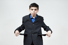 The boy is surprised and no money. The boy looks at the empty pockets in the jacket Stock Photo
