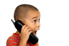 Boy surprised on telephone. Horizontal portrait of a young boy with a shocked expression talking on a phone royalty free stock image