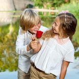 Boy surprising girl with flower. Stock Photo