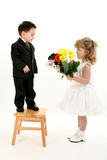 Boy Surprising Girl With Flowers. Toddler boy in suit giving flowers to pretty little girl in pageant dress. Shot in studio over white Stock Photography