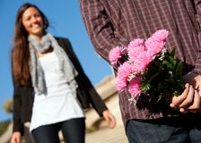 Boy surprising girlfriend with flowers Royalty Free Stock Photography