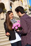 Boy surprising his girlfriend with flowers Stock Images