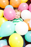 Boy surrounded by baloons Royalty Free Stock Image