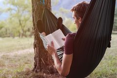 Young man reading a book on a hammock stock image