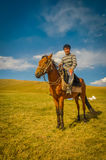 Boy in sweater on horse in Kyrgyzstan Royalty Free Stock Photos