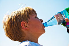 Boy is sweating and thursty. From doing sports and drinks mineral water out of a bottle stock photo