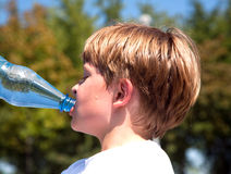 Boy is sweating and thursty. Young boy drinks water out of a bottle after sports royalty free stock image