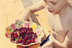 Boy with a sweet cherry Stock Photos