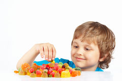 Boy with sweets and jelly candies on white background Royalty Free Stock Images