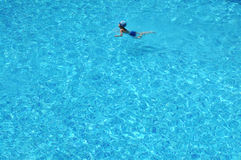 A boy swim in blue clear water Stock Images