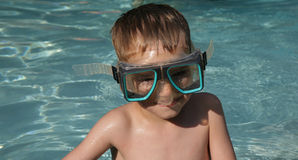 Boy in Swim Goggles. Young boy in adult swim goggles in a swimming pool Stock Photography