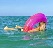 Boy in a swim ring has fun. Happy boy in a swim ring has fun in the ocean Stock Photo