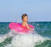 Boy in a swim ring has fun in the ocea Stock Photo