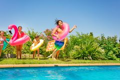 Boy in swim ring playing pool games with friends. Portrait of happy teenage boy in swim ring jumping into the water, playing pool games with friends royalty free stock photos