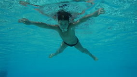 Boy swim in swimming pool, underwater slow motion