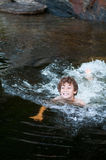 Boy swiming in a lake. Young boy playing in a lake in Haliburton County Ontario royalty free stock photos