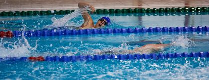 Boy swiming at sport pool. Young boy sportsman swimming at a contest Stock Photos