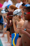 Boy Swimmers Get Ready To Swim Relay Race. LAWRENCEVILLE, GA - JUNE 14: A group of child male swimmers stand at edge of swimming pool, preparing to swim their Stock Images