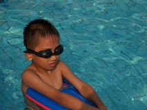 Boy swimming. A little asian boy in swimming pool Royalty Free Stock Photo