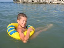 Boy swimming. Boy with swimming ring playing into the sea Stock Photo