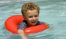 Boy Swimming. Young boy in float ring in swimming pool Stock Image