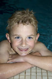 Boy Swimming. Six year old caucasian boy resting on the edge of an indoor swimming pool Stock Photo