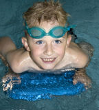 Boy Swimming. Six year old caucasian boy in a swimming pool with goggles and a blue kickboard Royalty Free Stock Images