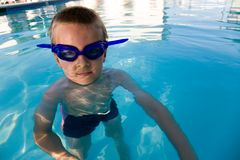 Boy swimming. Young boy wearing diving mask or goggles in the swimming pool afternoon Stock Images