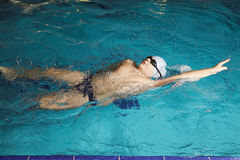 Boy swimming back stroke Stock Photos