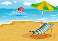 A boy swimming at the beach with a chair and an umbrella Royalty Free Stock Photography