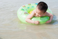 Boy swimming. Chinese boy swimming on beach with swim ring royalty free stock photography