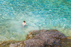 Boy swimming in crystal clear turquoise water Stock Photos
