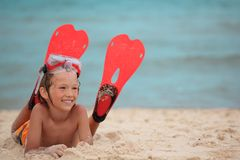 Boy with swimming fins on beach. Happy boy with swimming fins, laying on a sandy beach stock photo