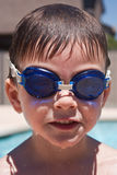 Boy with swimming goggles. Boy smiling by the pool while wearing swimming goggles Stock Images