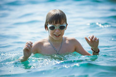 Boy in swimming goggles on sea. Portrait of playful boy in swimming goggles on sea Stock Photo