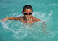 Boy swimming with great fun. An Asian boy swimming in the swimming pool with great fun in summer Royalty Free Stock Photo